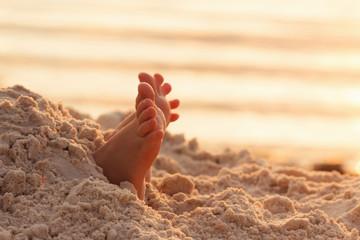 Closeup child kid feet on white sand beach.