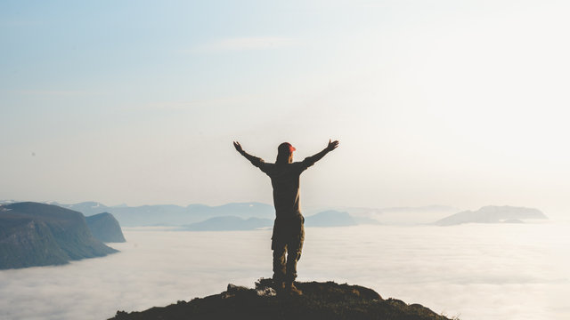 Young man stand on top of mountain top with hands raised in the air. Success and risk concept.