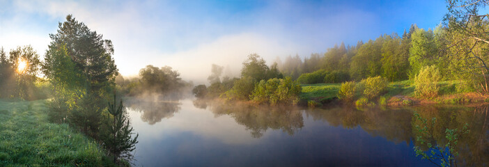 rural panorama with river, fog and forest at sunrise Fototapete