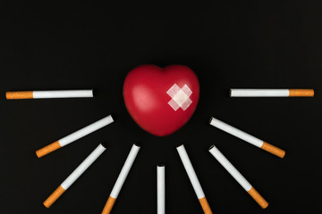 smoking kills concept, red heart symbol with adhesive plaster among the cigarettes on dark background