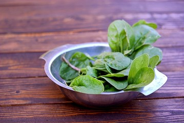 Fresh spinach leaves in a metal bowl on a wooden table. The concept of a healthy diet.