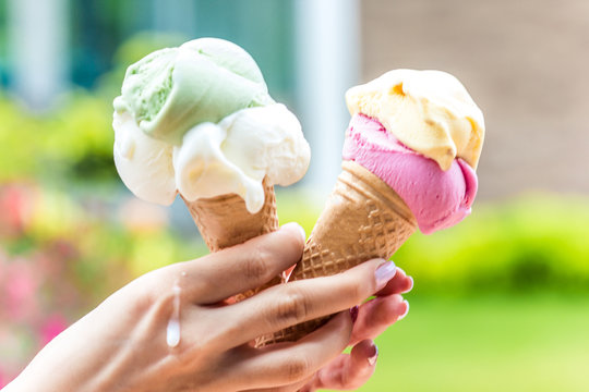 Two horns with ice cream in hot weather in a girl's hand