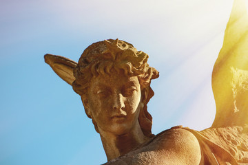 Antique statue of gold angel in the sunlight. (religion, faith, death, resurrection, eternity concept)