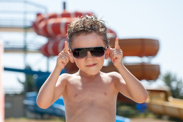 cool funny cute kid in sunglasses in water park in summer sunny day