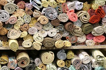 dozens of rolls of precious fabrics on the shelves