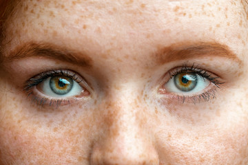 Close up eyes of young red ginger freckled woman with perfect healthy freckled skin, looking at camera. Ophthalmology, Vision care