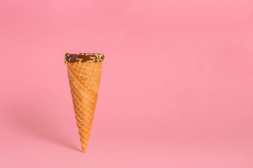 funny creative concept of close up empty wafer cone with chocolate glaze and colorful sprinkles over pastel pink background