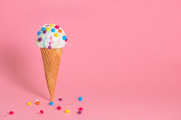 summer funny creative concept of wafer cone with melting ice cream covered and strewed colorful chocolate confetti on pink background