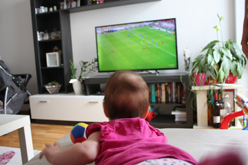 baby watching a soccer on TV