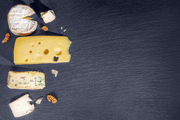top view of tasty various types of cheese on black slate stone background, Italian, French food, concept of dairy products