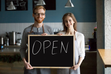 Smiling waiter and waitress holding chalkboard with open sign, cafe or coffee shop house business owners partners looking at camera welcoming inviting advertising new cafeteria bistro bar, portrait