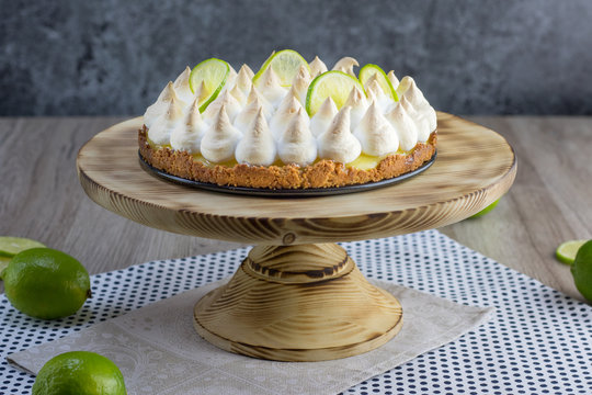 Lime meringue cake on wooden plate with slices of lime