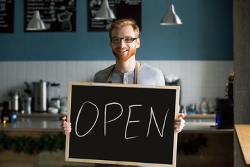 Redhead smiling man holding open sign inviting to cafeteria, bearded barista, waiter or business owner looking at camera presenting coffee shop welcoming to public place, new cafe concept, portrait