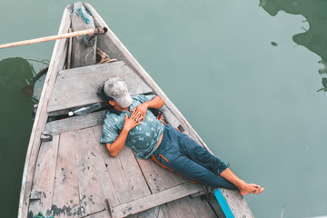 Man sleeping on a old wooden boat