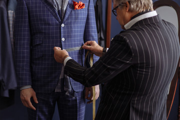 Mature professional Tailor taking measurements for sewing suit at tailors shop. Man with measuring tape busy. Exclusive Custom Made Cloth Concept.