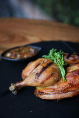 Grilled chicken on black dish wood background