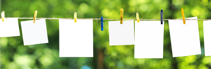 Empty paper sheet frames hanged by colored clothespins on green leaves nature  background. Blank cards on rope. Mock up for display of design, memo backdrop. Pieces of paper, posters. Ecology concept