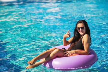 pretty brunette lady in black bikini sitting on the rubber ring in the swimming pool. Summer Vacation. Enjoying suntan. Weekend on resort