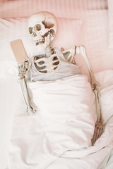 Human skeleton with phone in hand lies in bed