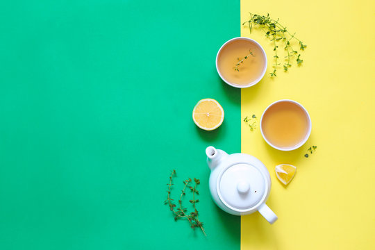 Herbal tea of thyme with lemon and other herbs on a colorful yellow green background.