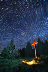 rotating star trails with illuminated wooden Christian cross