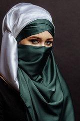 close up side view shot of attractive stylish Muslim woman isolated on the black background