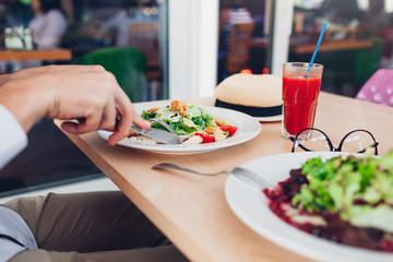 Man eating Caesar salad in restaurant. Having tasty lunch. Healthy food concept.
