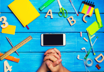 The student crossed his hands in front of a mobile phone in the workplace. A place for text. A student is looking at a mobile phone. Creative clutter on a blue wooden background. concept of education.