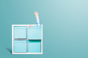 Fist pulled out of the drawer. Victory gesture. White dresser with blue drawers and shelves held by hand on a pastel blue background. Concept of minimalism and retro style.