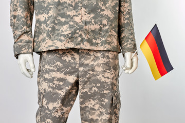 Patriotic german soldier concept. Mannequin in military uniform with deutsch flag. White isolated background.