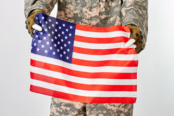 Soldier holding american flag. Portrait of mannequin in military camouflage. White isolated background.