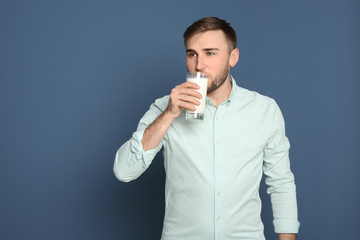 Young man drinking tasty milk on color background