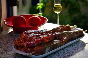 Grillfleisch in Schale auf einem Tisch mit Äpfeln und Glas