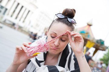 Young woman looking in a plastic cup full of candies