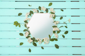 Mirror decorated with flowers on color wooden background