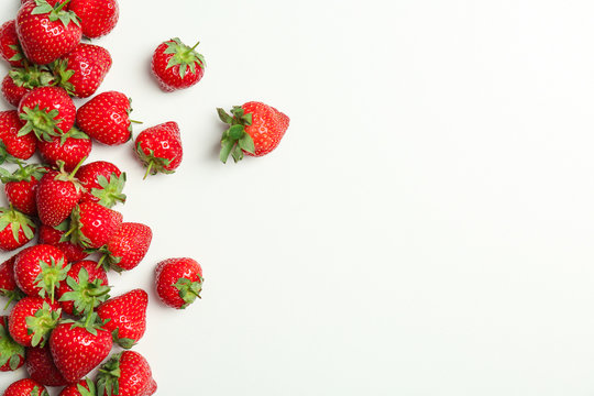 Flat lay composition with with tasty ripe strawberries on light background
