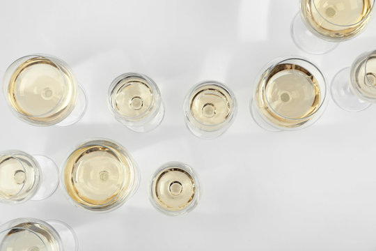 Glass of expensive white wine on light background, top view