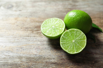 Fresh ripe green limes on wooden background