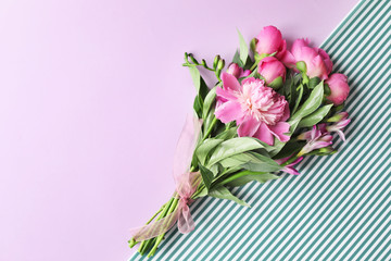 Bouquet of beautiful peony flowers on color background, top view