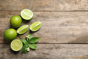Composition with fresh ripe limes on wooden background, top view