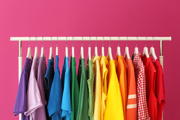 Rack with rainbow clothes on color background