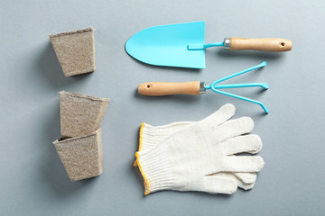 Flat lay composition with professional gardening tools on grey background