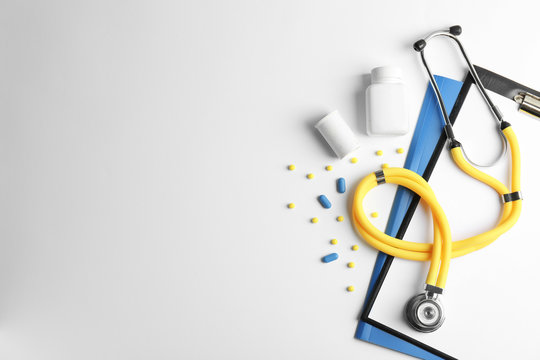 Stethoscope, clipboard and pills on light background, top view. Medical equipment