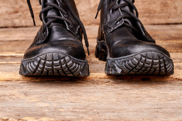Cropped image of black boots. Wooden desk surface background.
