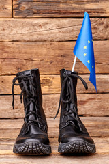 Combat boots with flag of european union. Brown wooden desk surface background.