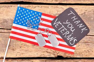 American flag and dog tags. Wooden desk background.