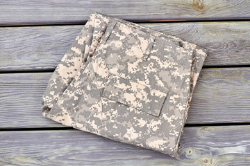 Folded camouflage pants on wood. Close up, top view.