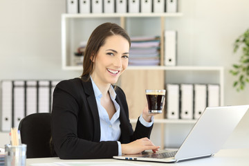 Office worker holding a coffee cup looking at camera