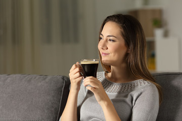 Satisfied woman enjoying coffee in the night