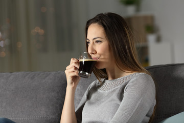 Relaxed woman drinking decaffeinated coffee in the night
